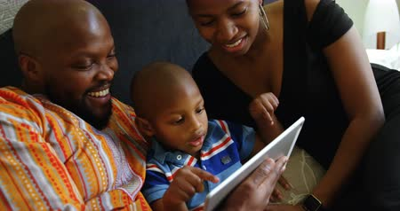 domy : Front view of smiling African american parents and son using digital tablet on bed at home. 4k