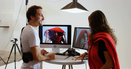 editor : Side view of Caucasian male photographer showing photos to female model on computer at photo studio. They are interacting with each other. 4k
