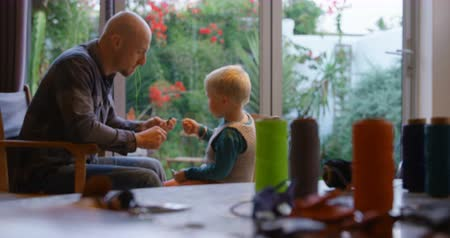 stiksel : Side view of Caucasian father and son stitching keychain at home. Various thread rolls on a table in the foreground. 4k