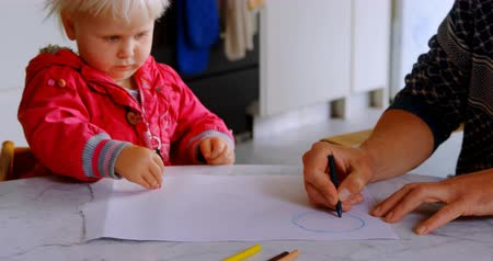 реальный : Front view of Caucasian father helping his daughter drawing at home. Son drawing on book. 4k