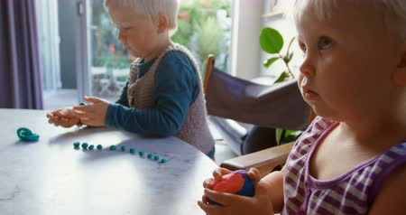 homely : High angle view of Caucasian kids playing with clay in a comfortable home. They are sitting at table 4k