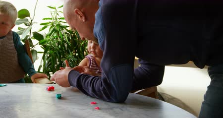 ártatlanság : Front view of Caucasian father and children playing together with clay in a comfortable home. They are sitting at table 4k Stock mozgókép
