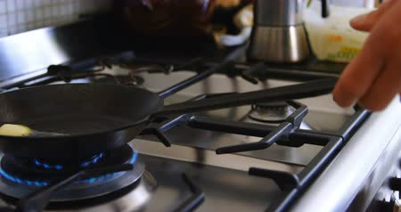 gas burner flame : Mid section of Caucasian man holding a pan on gas stove hob in kitchen at home. He is preparing food 4k