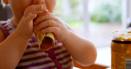 ártatlanság : Front view of Caucasian girl eating pancakes at home, while looking at camera 4k