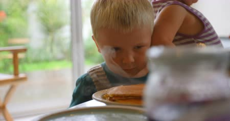 palačinka : Front view of Caucasian siblings looking at pancakes on dining table at home. They are sitting at dining table 4k