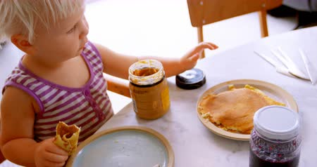lids : Front view of Caucasian girl eating pancake at home, while sitting at dining table 4k Stock Footage