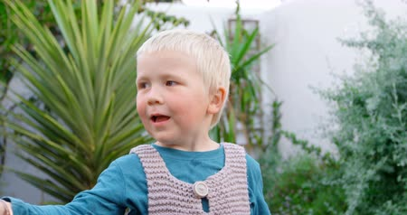 fragilidade : Front view of Caucasian boy playing with bubble wand in garden. He is smiling and having fun 4k
