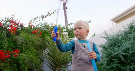 kırılganlık : Front view of Caucasian boy playing with bubble wand in garden. He is smiling and having fun 4k