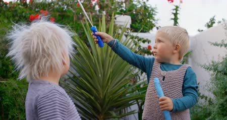 fragilidade : Front view of Caucasian siblings playing with bubble wand in garden. 4k