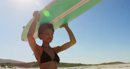 cabeça e ombros : Low angle view of young African American female surfer smiling and carrying surfboard on her head at beach 4k Vídeos