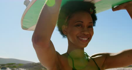 hlava a ramena : Close-up of young African American female surfer smiling and looking at the camera while carrying surfboard on her head at beach 4k