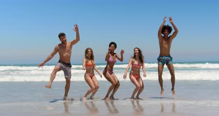teljes hosszúságú : Front view of young multi ethnic friends jumping together while smiling and looking at the camera at beach on a sunny day 4k