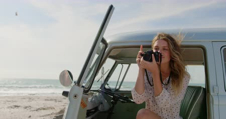 generation z : Front view of young Caucasian woman taking photos with digital camera in camper van at beach 4k Stock Footage