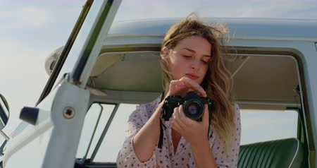 recuerdos : Front view of young Caucasian woman reviewing photos on digital camera in camper van at beach while smiling and looking away 4k