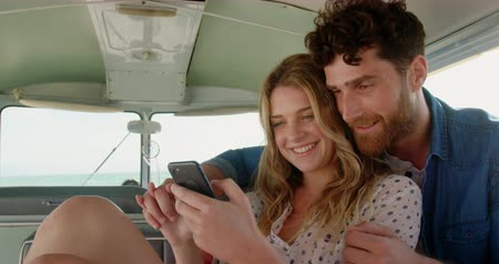 furgone : Front view of young Caucasian couple using mobile phone in camper van at beach 4k