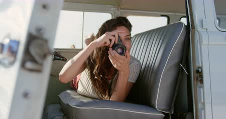 camioneta : Front view of beautiful young Caucasian woman taking photo with digital camera in camper van while lying on seat 4k Archivo de Video