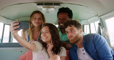 fotografando : Front view of group of young Multi-ethnic friends taking selfie in camper van at beach. They are smiling and having fun 4k