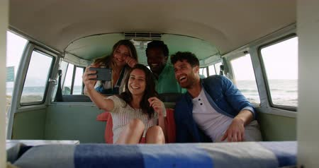 высокой четкости : Front view of group of young Multi-ethnic friends taking selfie in camper van at beach. They are smiling and having fun 4k