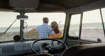 cabeça e ombros : Rear view of Caucasian couple standing near camper van on the beach. Man is pointing at distant 4k