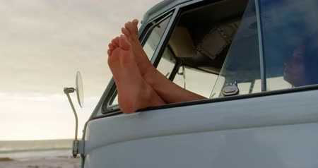 boso : Side view of Caucasian woman relaxing with feet up in camper van at beach. She is looking away 4k