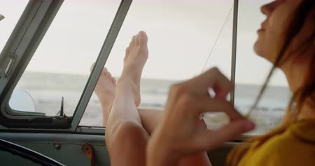 teljes hosszúságú : Rear view of Caucasian woman relaxing with feet up in camper van at beach. She is looking away 4k