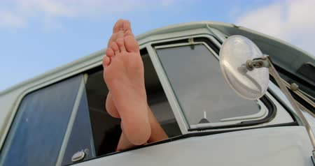 side road : Low section of Caucasian woman relaxing with feet up in camper van at beach. She is barefoot 4k