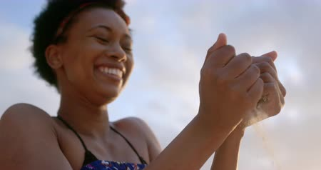 etnia africano : Low angle view of African american woman playing with sand on the beach. She is smiling and having fun 4k
