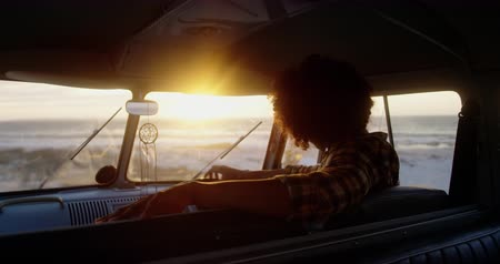 contemplação : Rear view of African American man relaxing in camper van at beach. He is holding steering wheel 4k