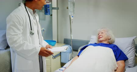glicose : Front view of Asian male doctor interacting with active senior patient in the ward at hospital. He is holding clipboard 4k