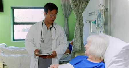 intravenous drip : Front view of Asian male doctor interacting with active senior patient in the ward at hospital. He is holding digital tablet 4k Stock Footage