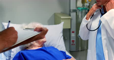 saline drip : Front view of Caucasian female doctor examining active senior patient in the ward at hospital. She is using stethoscope 4k Stock Footage