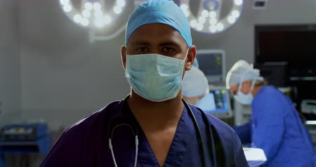 surgical light : Front view of African-american male surgeon standing in the operation theater at hospital. Surgeons performing operation in the background 4k