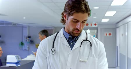 panoya : Front view of Caucasian male doctor writing on clipboard in the hospital. He is looking at camera 4k