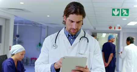 görgetés : Front view of thoughtful Caucasian male doctor using digital tablet in the hospital. Medical staff working in the background 4k Stock mozgókép