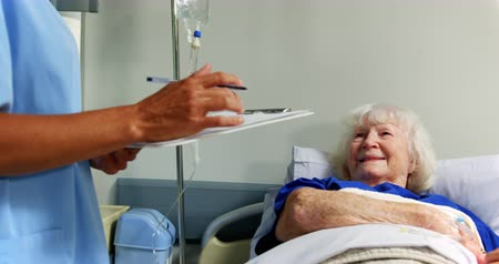 saline drip : Side view of Caucasian female doctor interacting with senior patient in the ward at hospital. Senior patient relaxing on hospital bed 4k