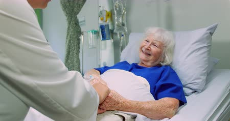 comprimento total : Side view of African American Female doctor interacting with active senior patient in the ward at hospital. She is consoling her 4k Stock Footage