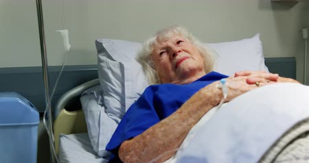 intravenous drip : Front view of active senior patient relaxing in the ward at hospital. She is looking away 4k Stock Footage