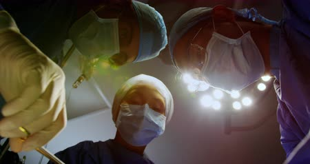 surgical light : Low angle view of surgeons performing operation in operation theater at hospital. They are holding surgical instruments 4k Stock Footage