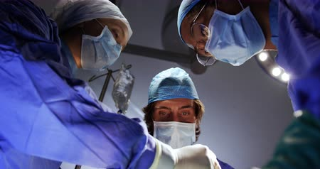 surgical light : Low angle view of surgeons performing operation in operation theater at hospital. They are interacting with each other 4k