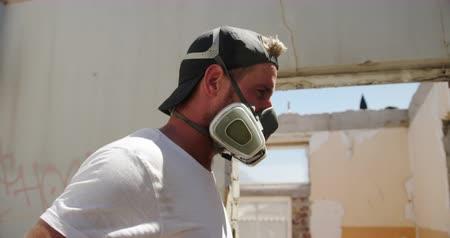kaplanmış : Side view of Caucasian graffiti artist wearing protective mask in the sunshine. He is getting ready for spray painting 4k