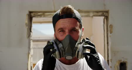 vandalismo : Front view of Caucasian graffiti artist wearing protective mask in the sunshine. He is looking at camera 4k Stock Footage