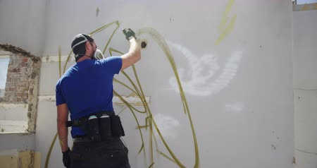 vandalismo : Rear view of Caucasian graffiti artist painting with aerosol spray on the wall. He is wearing protective mask 4k Stock Footage
