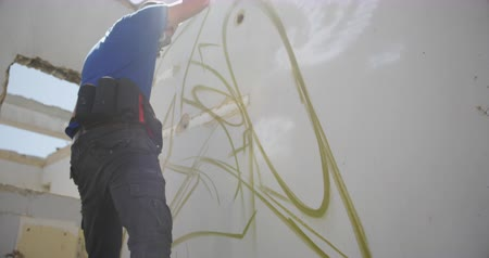 kaplanmış : Low angle view of Caucasian graffiti artist painting with aerosol spray on the wall. He is wearing protective mask 4k