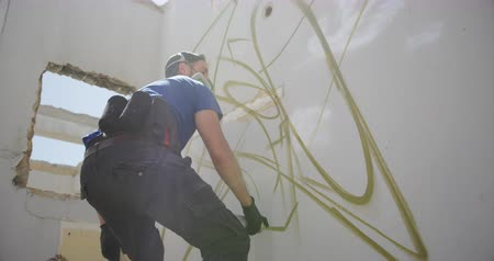 enrobé : Low angle view of Caucasian graffiti artist painting with aérosol spray on the wall. Il porte un masque de protection 4k