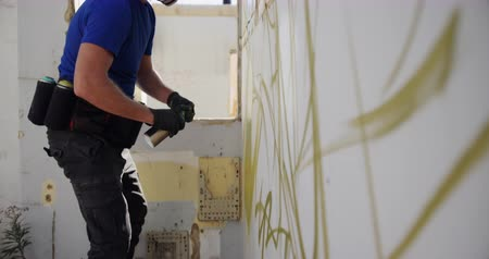 покрытый : Side view of Caucasian graffiti artist painting with aerosol spray on the wall. He is wearing protective mask 4k