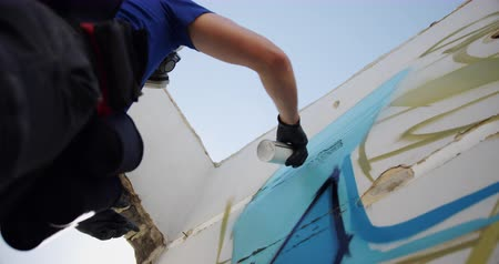 покрытый : Low angle view of Caucasian graffiti artist painting with aerosol spray on the wall. He is wearing protective mask 4k