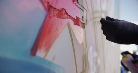 vandalismo : Low angle view of Caucasian graffiti artist touching the painted wall. He is shaking aerosol can 4k Stock Footage