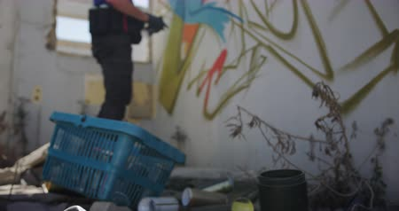 покрытый : Side view of Caucasian graffiti artist painting with aerosol spray on the wall. Protective mask on the ground 4k