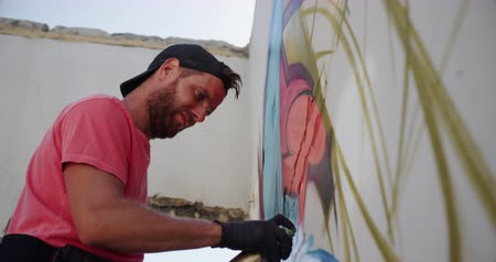 sikátorban : Low angle view of Caucasian graffiti artist painting with aerosol spray on the wall. He is creative 4k