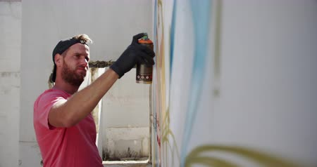 vandalismo : Side view of Caucasian graffiti artist painting with aerosol spray on the wall. He is creative 4k